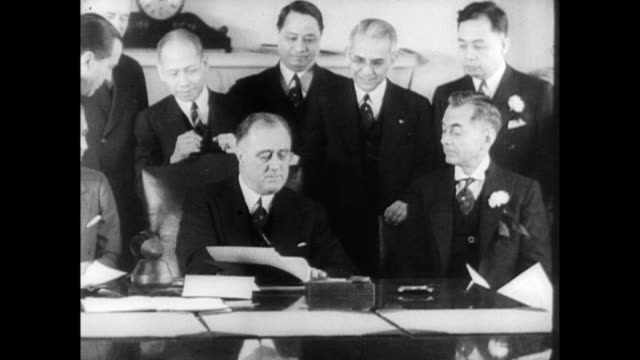 vidéos et rushes de president roosevelt seated behind desk signs approval of philippine constitution surrounded by government officials / smiling fdr signs and then... - 1935