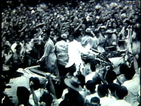 president sukarno standing in opentop car and waving as it moves through large crowd of cheering supporters / indonesia - människolem bildbanksvideor och videomaterial från bakom kulisserna