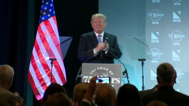 president trump walks across stage and hugs the american flag during the national federation of independent businesses 75th anniversary celebration... - flag stock videos & royalty-free footage