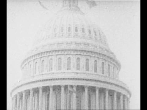 US President Woodrow Wilson and wife Edith stand with dignitaries / pan down EXT US Capitol with US flags hanging over dais as spectators stand at...