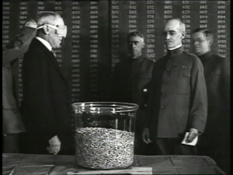President Woodrow Wilson being blindfolded by officer officer guiding hand of president into glass bowl filled w/ lottery numbers Wilson taking out...