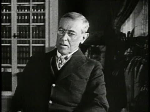 WILSON President Woodrow Wilson sitting in chair nods slightly as if listening CU Presidential Seal President Woodrow Wilson sitting at desk dipping...
