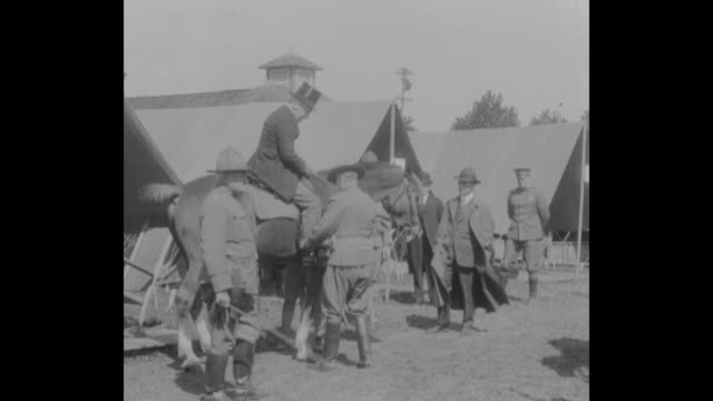 stockvideo's en b-roll-footage met ws president woodrow wilson stands near his car after arriving / wilson and camp's commanding officer rock on rocking chairs in the co tent / ws us... - hogehoed