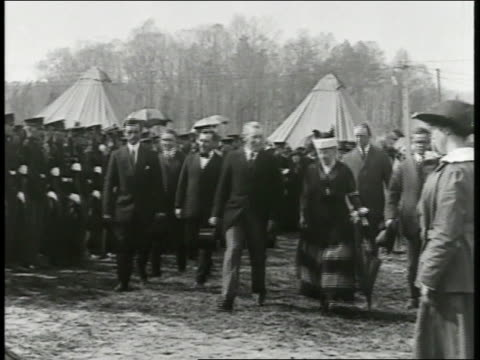 President Woodrow Wilson walking w/ May Queen Consort of Edward V others through WWI soldier's camp
