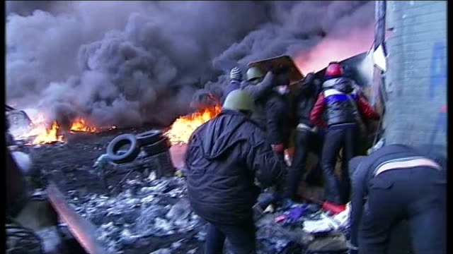 president yanukovich calls emergency session of parliament; day sun in sky behind clouds of smoke various shots demonstrators throwing tyres onto... - ウクライナ点の映像素材/bロール