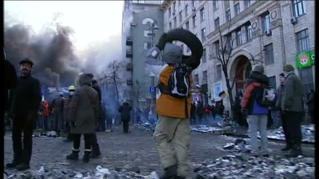 president yanukovich calls emergency session of parliament; demonstrators pulling pile of tyres along on metal board various shots people carrying... - ukraine stock-videos und b-roll-filmmaterial