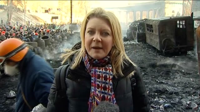 President Yanukovich calls emergency session of parliament UKRAINE Kiev EXT Reporter to camera with protesters and tyre barricades behind Smouldering...