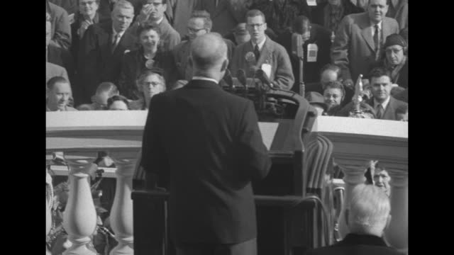 Presidentelect Dwight Eisenhower speaks from podium Vice Presidentelect Richard Nixon is seated on his right / from behind Supreme Court Chief...