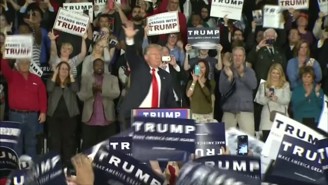 vídeos de stock e filmes b-roll de presidential candidate donald trump calls for all muslims to be banned from us; usa: donald trump at podium as supporters wave 'trump' placards - partidário