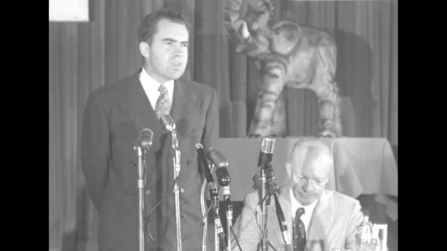 ms presidential candidate dwight d eisenhower's running mate richard m nixon stands at microphones on table and speaks eisenhower sits at table... - richard nixon stock-videos und b-roll-filmmaterial