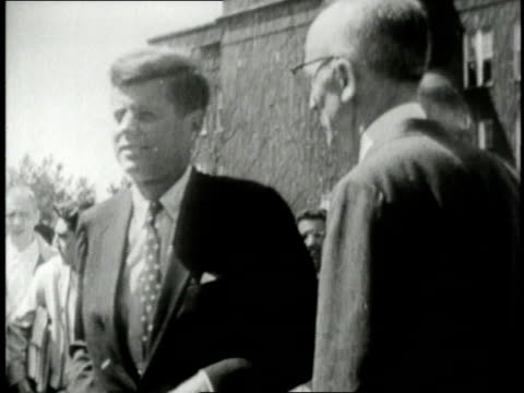Presidential candidate JFK campaigning in West Virginia by walking in streets and shaking hands with pedestrians / United States