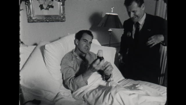 presidential candidate richard nixon in hospital bed at the walter reed army medical center for a staph infection visited by new york governor nelson... - ネルソン a ロッカフェラー点の映像素材/bロール