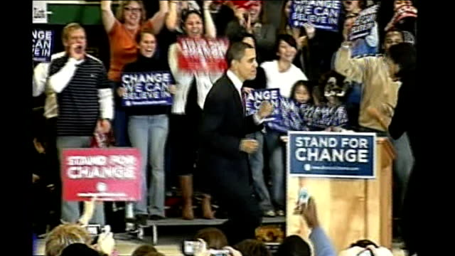 iowa caucuses underway barack obama onto stage at rally and hugs his wife - バラク・オバマ点の映像素材/bロール