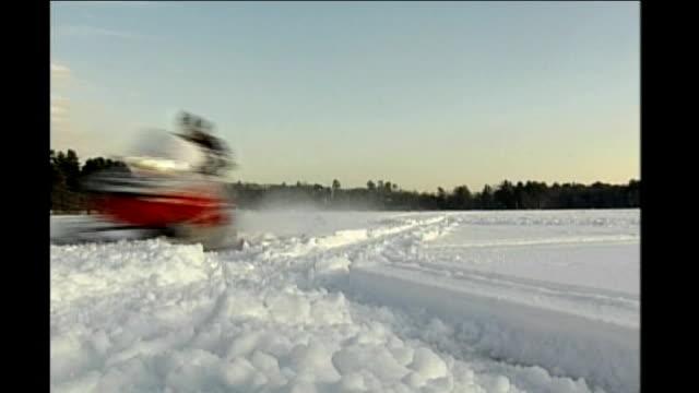 vídeos de stock, filmes e b-roll de new hampshire primary voting day person riding snowmobile across snowcovered field men icefishing snow and ice melting - eleição primária