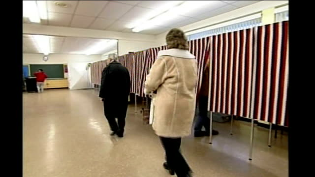 stockvideo's en b-roll-footage met new hampshire primary voting manchester voters along to polling booths and ballot box - stembus