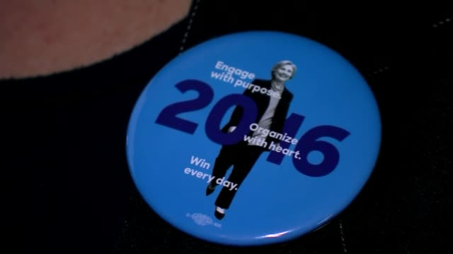 Candidates make final push for votes USA INT Television screens showing news programme Close shot Hillary Clinton badge 'Engage with purpose organise...