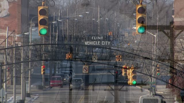 vidéos et rushes de clinton and sanders debate in flint michigan t21011607 / tx high angle shot road with traffic and 'flint vehicle city' sign at traffic lights flint... - michigan