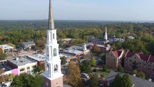 Latest developments Chapel Hill AIR VIEW / AERIAL / DRONE shot of town centre buildings and church spires/ Students walking in gorunds of college...