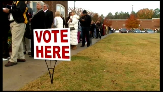 stockvideo's en b-roll-footage met polling day wisconsin people along in queue 'vote here' sign nextto people queuing people voting in polling booths man putting vote into machine back... - stembus