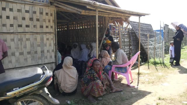 aung san suu kyi would rule 'above the president' if her party wins woman along past makeshift dwellings at camp for displaced rohingya people young... - makeshift stock videos and b-roll footage