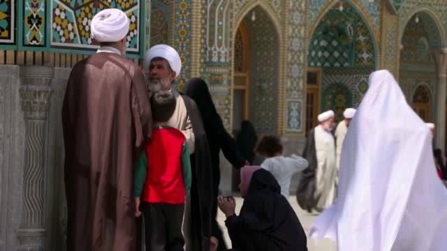 vídeos de stock e filmes b-roll de city of qom iran qom ext women men and children milling about with grand mosque in background muslim clerics along people along through grounds of... - islamismo