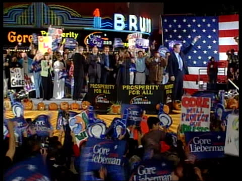 vídeos y material grabado en eventos de stock de presidential elections; itn california: ext at night tls al gore on stage as rally as supporters wave banners in f/g gore waving to crowd gv gore on... - gore
