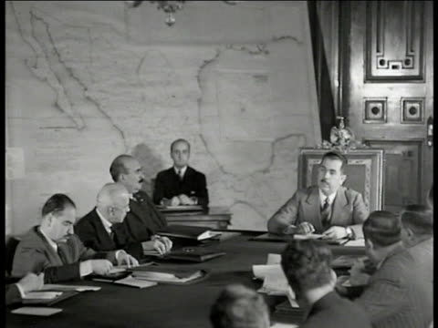 presidential palace building int ws mexican president lazaro cardenas at head of table w/ officials men in meeting map of mexico on wall bg ms... - 外交点の映像素材/bロール