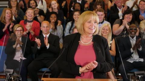 4k: raduno per la campagna presidenziale / politica elezione - la candidata femminile parla ai sostenitori in auditorium - uomo politico video stock e b–roll