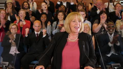 4k: raduno per la campagna presidenziale / politica - la candidata femminile parla ai sostenitori in auditorium - uomo politico video stock e b–roll