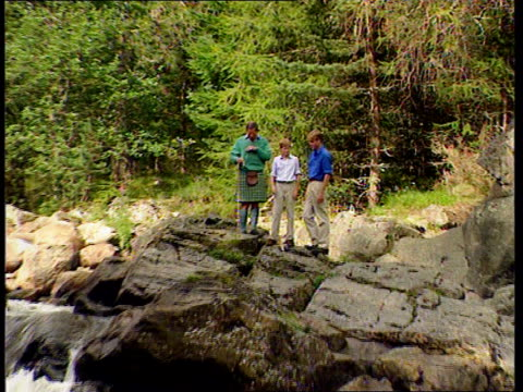 NICHOLAS LIB SCOTLAND Balmoral Prince Charles standing with Princes William and Harry on rocks above waterfall for photo opportunity ZOOM IN TBV...