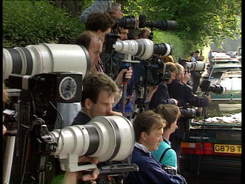 Press coverage of royals NAF London Notting Hill Gate LMS Press photographers lined up on pavement MS Ditto TMS Photographers PAN LR MS Car carrying...