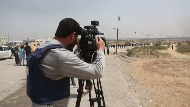 press members cover the protest near the israeli border fence, east of gaza city in the central gaza strip on april 13, 2018. several thousand gazans... - 2018 gaza border protests stock videos & royalty-free footage