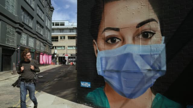 a press photographer walks past graffiti by artist graffiti life in east london that depicts a nhs health worker wearing a ppe face mask due to the... - artist stock videos & royalty-free footage