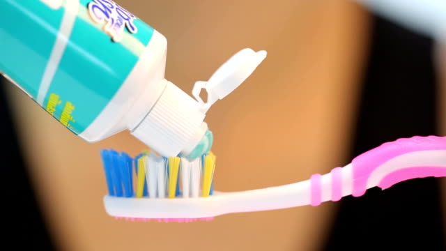 press toothpaste to toothbrush for brushing your tooth - teeth whitening stock videos and b-roll footage