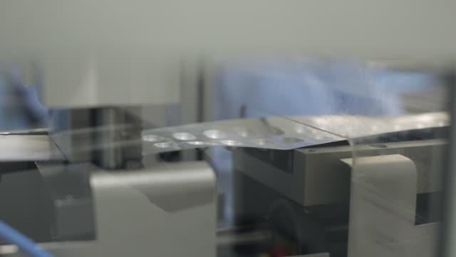 pressing machine creating pockets for capsule blister packaging - läkemedelsfabrik bildbanksvideor och videomaterial från bakom kulisserna