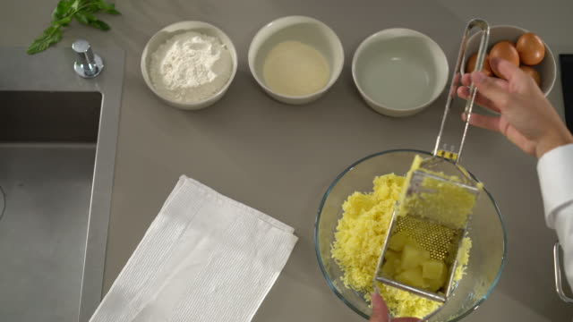 4k pressing potatoes through ricer in kitchen top view - prepared potato stock videos & royalty-free footage