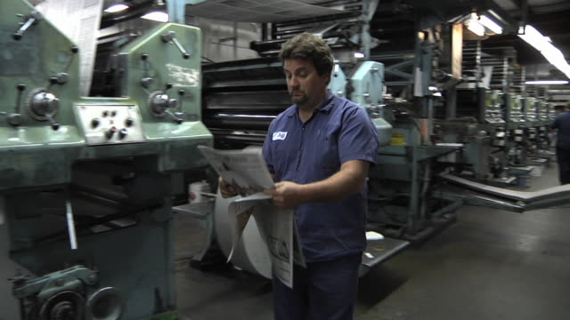 ws pan pressmen checking print quality of freshly printed edition and making adjustments at newspaper printing plant / powers, michigan, usa - female with group of males stock videos & royalty-free footage