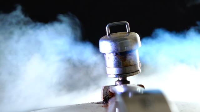 pressure cooking valve releasing steam in a black background, the process of cooking - 空気弁点の映像素材/bロール