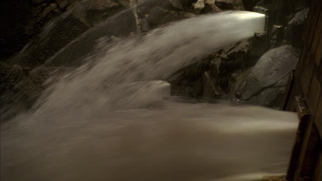 cs pressure release in old waterworks, with streams of water bursting through rock walls - breitwandformat stock-videos und b-roll-filmmaterial