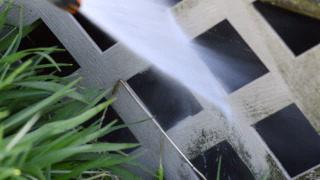 pressure washing vinyl lattice fence below deck - fence stock videos & royalty-free footage