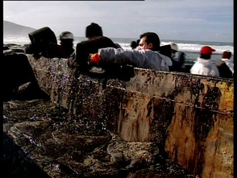 Prestige tanker Oil Spill, 2002: clean-up team empty buckets of oil into skip, Northwest coast of Spain.