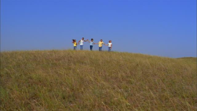 Preteen children hold hands and run down a grassy hill.