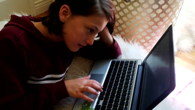 preteen female using laptop on furry bean bag and laughing at what she reads - bean bag stock videos & royalty-free footage