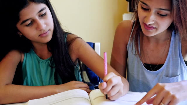 Preteen fille être tutored par sa grande sœur et faire des calculs devoirs