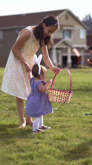 イースターエッグ狩りの屋外で彼女の妹を助けるプレティーンの女の子 - sunny点の映像素材/bロール