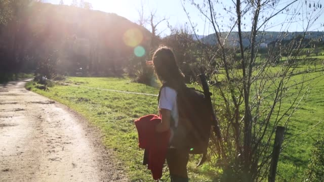 preteen girl hiking in nature, looking away in a bright sunny day - 手をかざす点の映像素材/bロール