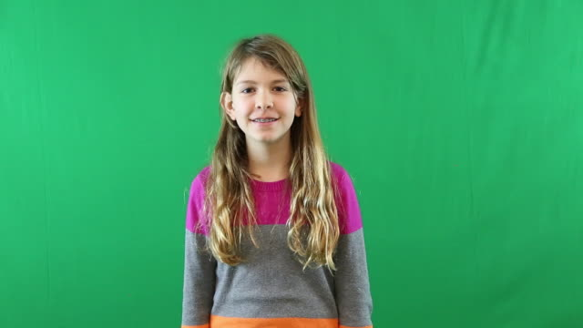 A preteen girl looking at the camera and smiling in front of a green screen