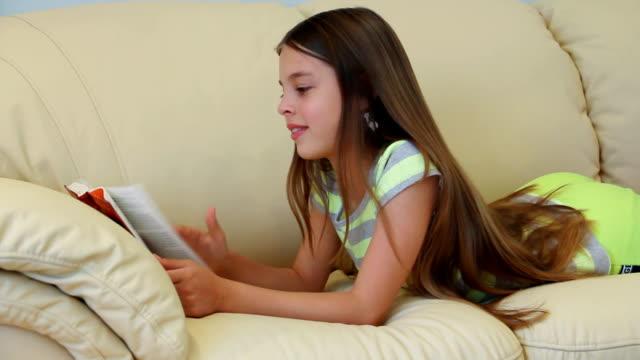Preteen girl reading a book.