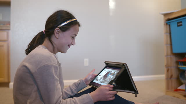 preteen girl using tablet computer at home to attend online class - digital native stock videos & royalty-free footage