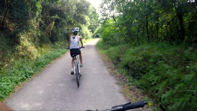preteen girl with helmet, braid and sport clothes riding on a bike in nature. - parte de una serie video stock e b–roll